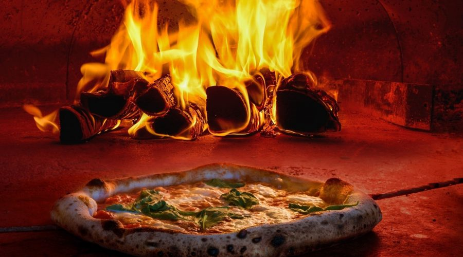 authentic italian pizza cooking in a wood fire pizza oven
